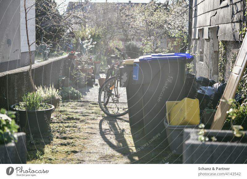 Hauseinfahrt mit Mülltonnen, Fahrrad und Blumenkübeln Einfahrt Hinterhof unordentlich renovierungsbedürftig Einfamilienhaus Prekariat Armut Arbeiter Pflanzkübel