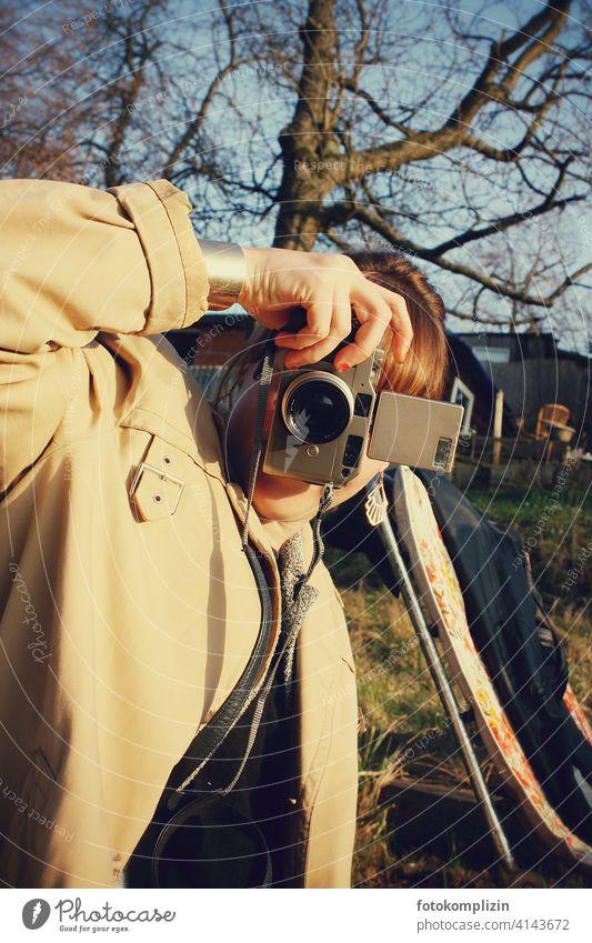 junge Frau beim Fotografieren mit einer analogen Kleinbildkamera analoge fotografie analoge Fotografie fotografierend retro retro-stil knipsen 35mm Fotokamera