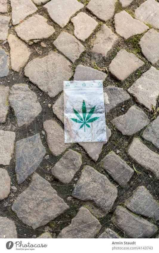 Cannabisblatt bedruckt auf einer kleinen Plastiktüte, die auf dem Bürgersteig liegt Sucht Hintergrund Tasche Blütenknospen Großstadt Kopfsteinpflaster