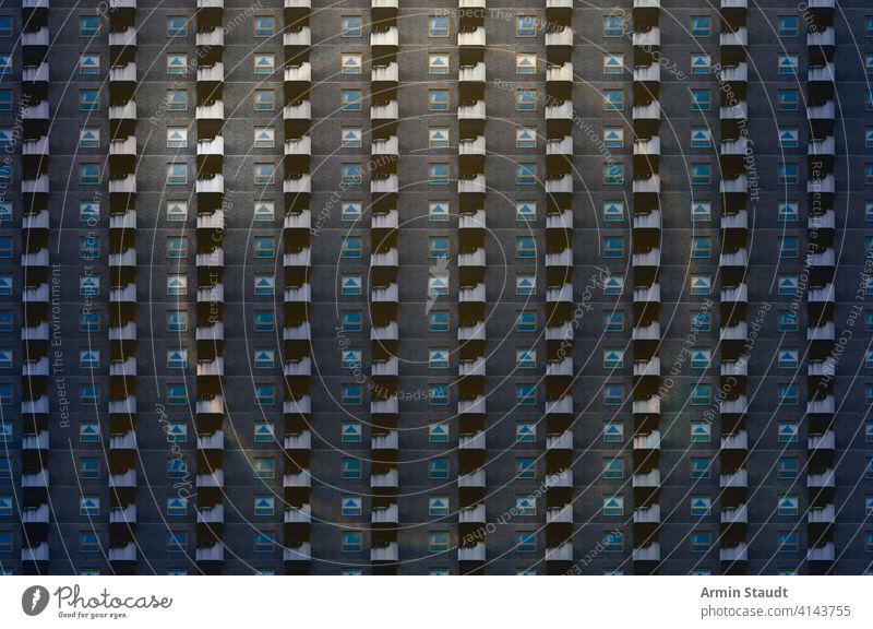 architektonisches Muster, dunkle Fassade mit Fenstern, Balkonen und runder Regenbogenfackel Überbevölkerung anonym Lifestyle Wolkenkratzer übergangslos
