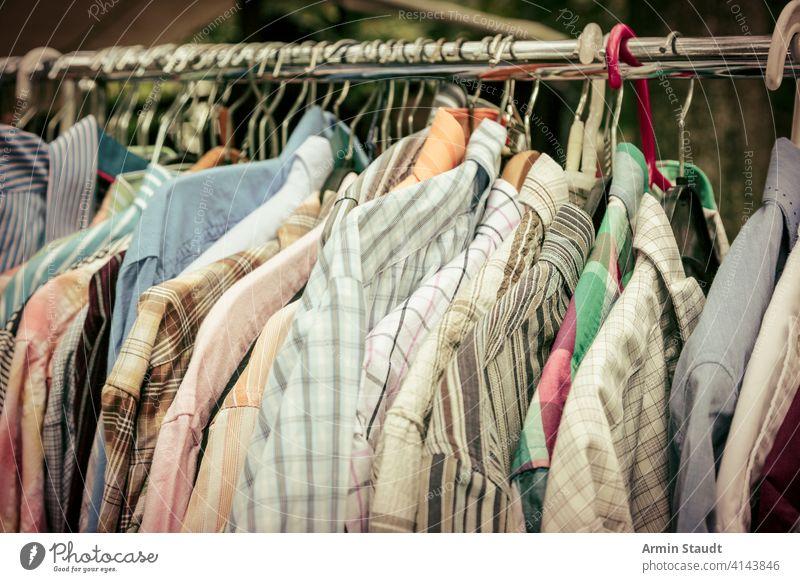 Kleidung auf einem Gestell auf einem Flohmarkt Überfluss Autokofferraumverkauf lässig Kleiderständer Bekleidung Mantel Farbfilter Konsumverhalten zu verkaufen