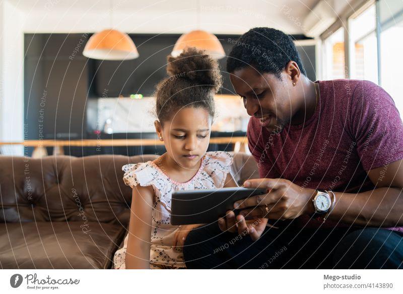 Vater und Tochter verwenden digitales Tablet zu Hause. monoparentiell spielen digitales Tablett Lifestyle Familie alleinerziehend im Innenbereich Aktivität