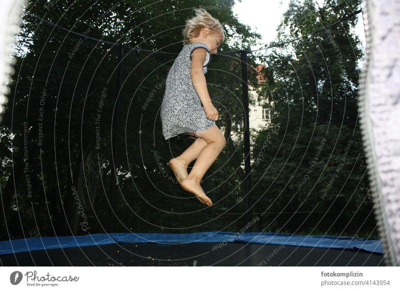 Kind hüpft auf einem Trampolin hüpfen Luftsprung Kinderspiel energiegeladen vitalität Freizeit & Hobby turnen fröhlich sich bewegen luftig Freude Sprung