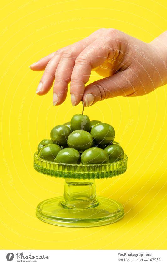Frau nimmt eine grüne Olive in die Hand. Essen frische Bio-Oliven olea europaea Amuse-Gueule Hintergrund Nahaufnahme Farbe farbenfroh Textfreiraum Küche