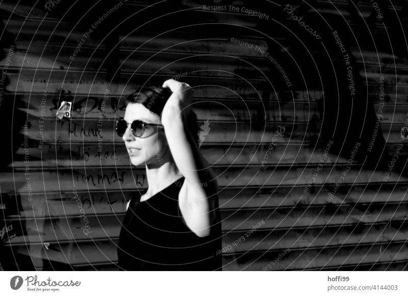 Die junge Frau mit Sonnenbrille geht vor eine geschlossenen Schaufenster der Sonne entgegen Junge Frau Frauenaugen Stadt Porträt Frauengesicht Jugendliche
