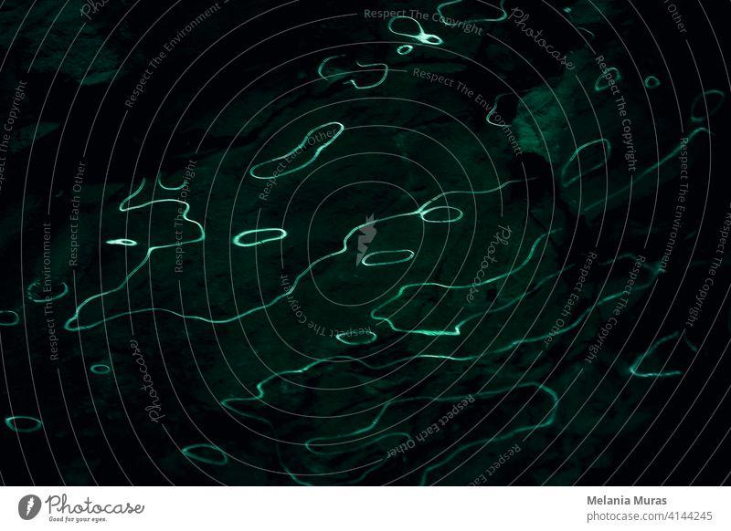 Wellen von Lichtreflexionen auf dunklem Hintergrund, felsig. Abstrakte Kurven von fluoreszierendem Licht. Dunkler Hintergrund mit organischen, flüssigen Lichtlinien.