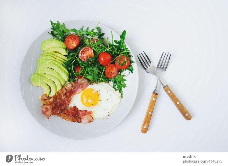 leckeres Frühstück - Spiegelei und Speck serviert mit Rucola-Tomaten-Salat und frischer Avocado auf weißem Teller Lebensmittel Mahlzeit Ei Morgen Gemüse Brunch