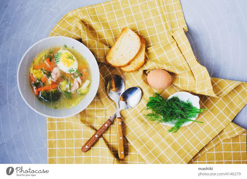 gesunde hausgemachte Hühnernudelsuppe mit Ei, Brokkoli und Karotten, serviert im Teller mit geröstetem Brot Nudel Suppe Hähnchen Gemüse Abendessen Lebensmittel