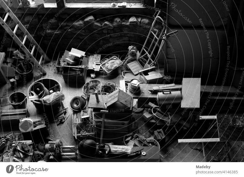 Werkzeug und Gegenstände in der Werkstatt eines Handwerker in einer alten Scheune auf einem Bauernhof in Rudersau bei Rottenbuch im Kreis Weilheim-Schongau in Oberbayern, fotografiert in klassischem Schwarzweiß