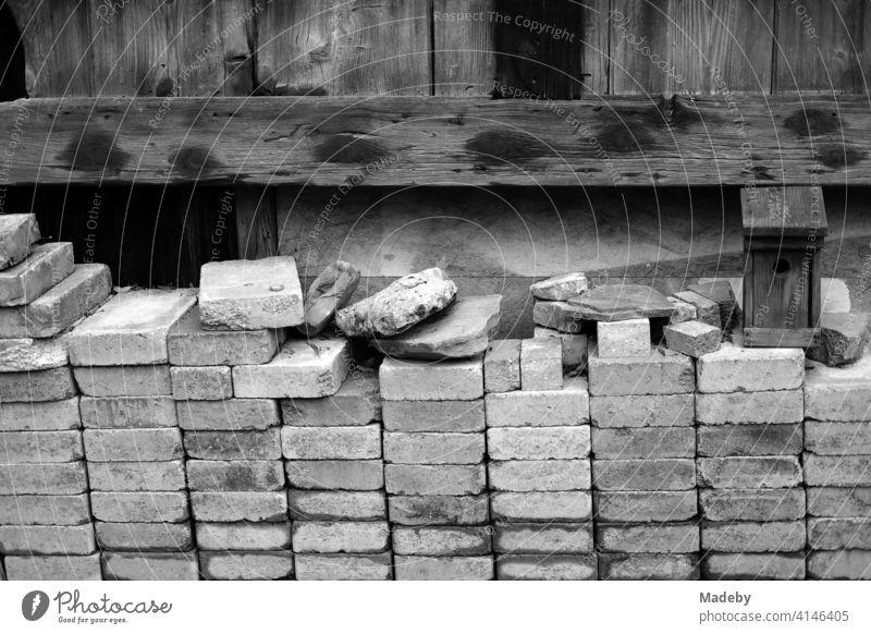Sorgfältig und ordentlich gestapelte Backsteine vor einer alten Scheune aus Holz auf einem Bauernhof in Rudersau bei Rottenbuch im Kreis Weilheim-Schongau in Obrbayern, fotografiert in klassischem Schwarzweiß