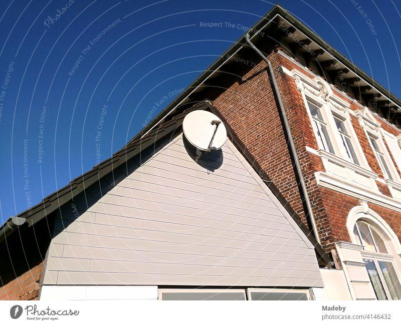 Satellitenschüsel im Spitzgiebel eines Nebengebäudes vor einem schönen Altbau im Sonnenschein in Lemgo bei Detmold in Ostwestfalen-Lippe Satellitenschüssel