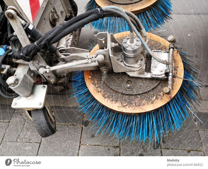 Kehrmaschine mit rotierenden blauen Borsten auf einem Gehweg in Offenbach am Main in Hessen Kehren Rotation Besen Reinigung Straßenreinigung Technik Sauberkeit