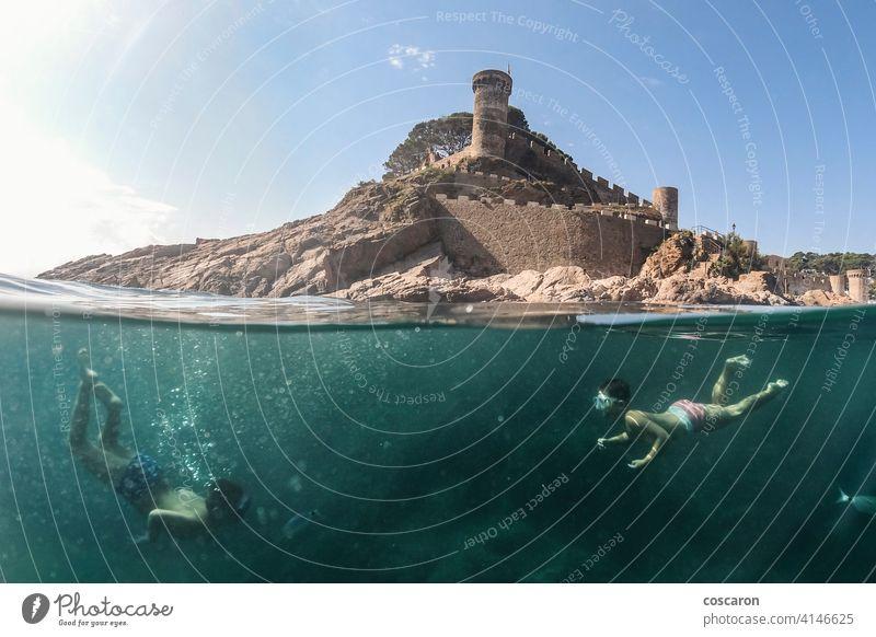 Zwei kleine Jungen schnorcheln mit einer Burg im Hintergrund Apnoe Strand Karibik Burg oder Schloss Kind Kindheit niedlich Sinkflug Taucher genießend Genuss