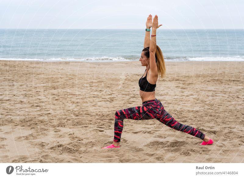 Junge fit attraktive weibliche üben Yoga Krieger eine Pose, Virabhadrasana posture.Athletic Frau arbeiten im Freien, am Strand am Meer, Lifestyle-Fitness-Training Konzept.