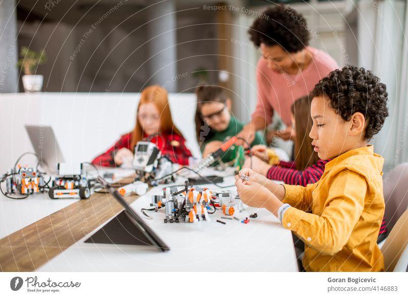 Glückliche Kinder mit ihren afroamerikanischen weiblichen Wissenschaft Lehrer mit Laptop Programmierung elektrische Spielzeuge und Roboter bei Robotik Klassenzimmer
