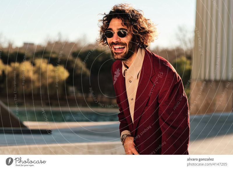 Selbstbewusster Mann, der lächelt, während er im Freien steht. Porträt Hipster urban Straße Kleidung stylisch Großstadt trendy Bekleidung Selbstvertrauen Stil