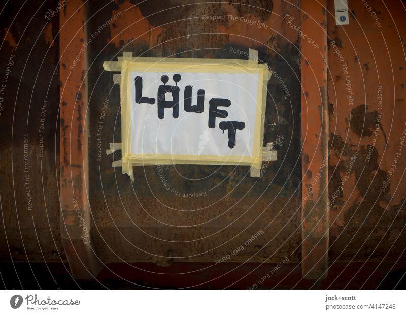 Läuft bei dir Zettel Papier angeklebt Großbuchstabe Kreativität läuft Wort Idee Deutsch Straßenkunst Subkultur Container Rost Zahn der Zeit Detailaufnahme