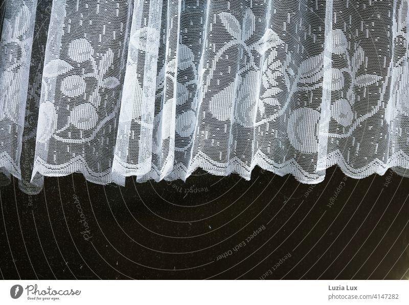 Eine zarte weiße Gardine, dahinter viel Dunkelheit. Vorhang Spitze schwarz Fenster Fensterscheibe dunkel strahlend Häusliches Leben Licht
