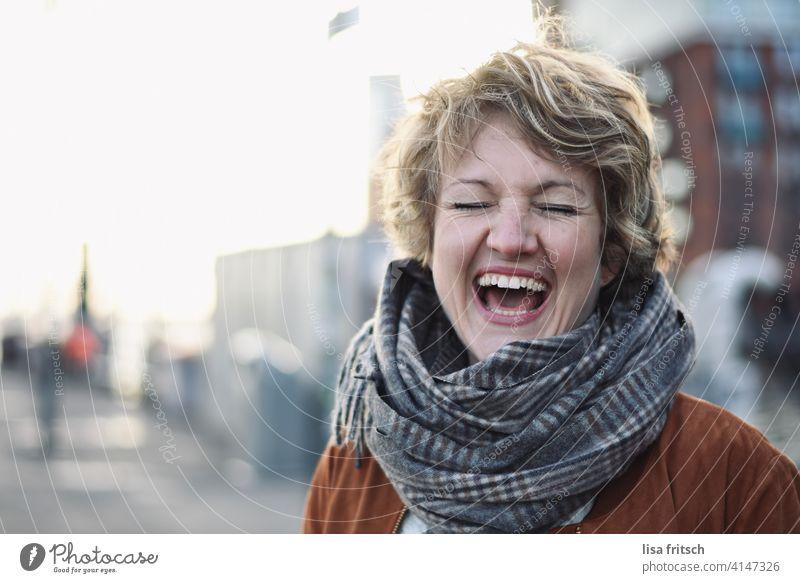 LACHEN Frau blond Locken kurzhaarig Kurzhaarschnitt Schal Augen geschlossen lachen Spaß haben Freude Spaßvogel glücklich ausgelassen Ausgelassenheit