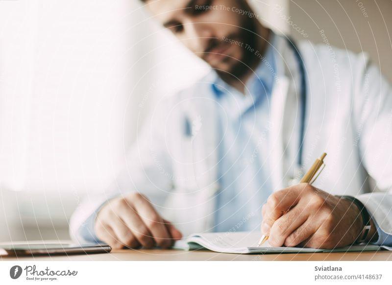Freundlicher junger männlicher Arzt mit orientalischem Aussehen sitzt an einem Schreibtisch in seinem Büro und macht sich Notizen in einem Notizbuch, Nahaufnahme