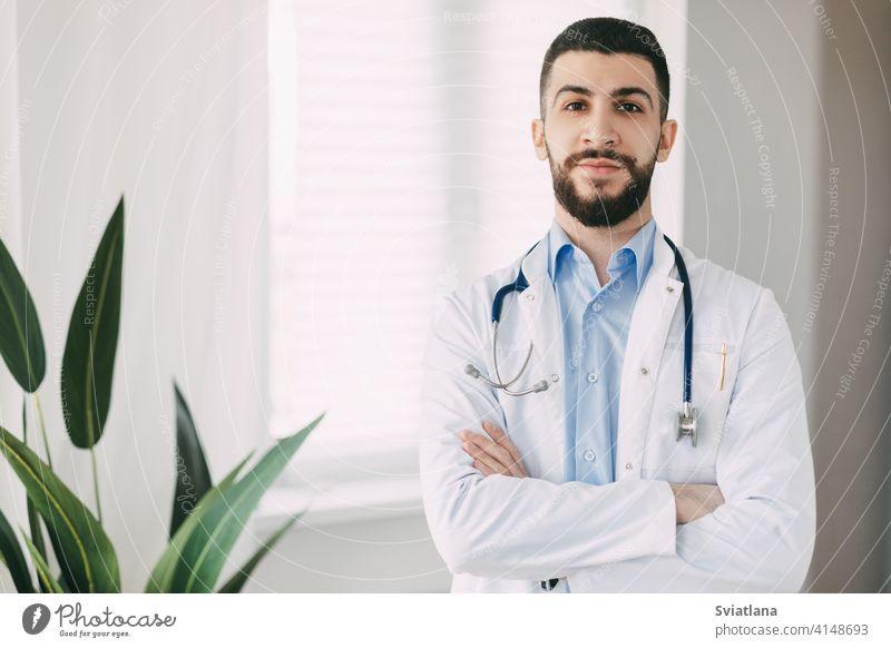 Lächelnder junger Arzt mit Stethoskopen und weißem Arztkittel steht mit verschränkten Armen in seinem Büro Medizin Mann Gesundheit medizinisch professionell