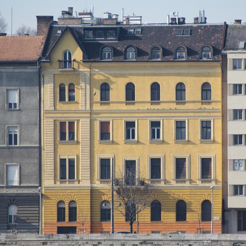 Budapester Stadthaus Fassade Architektur Uferbefestigung authentisch orange Stil Sonnenlicht Farbgestaltung Strukturen & Formen kahler Baum Häuserzeile