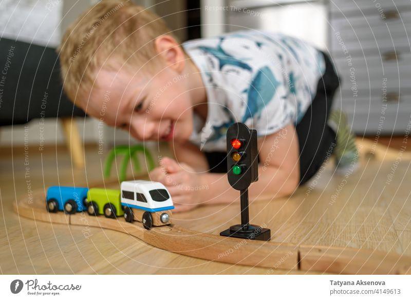 Kleiner Junge spielt Eisenbahn Kind Spielzeug spielen heimwärts Kindheit Spaß Freude Konstruktion Entwicklung Spielen Person im Innenbereich Vorschule Glück