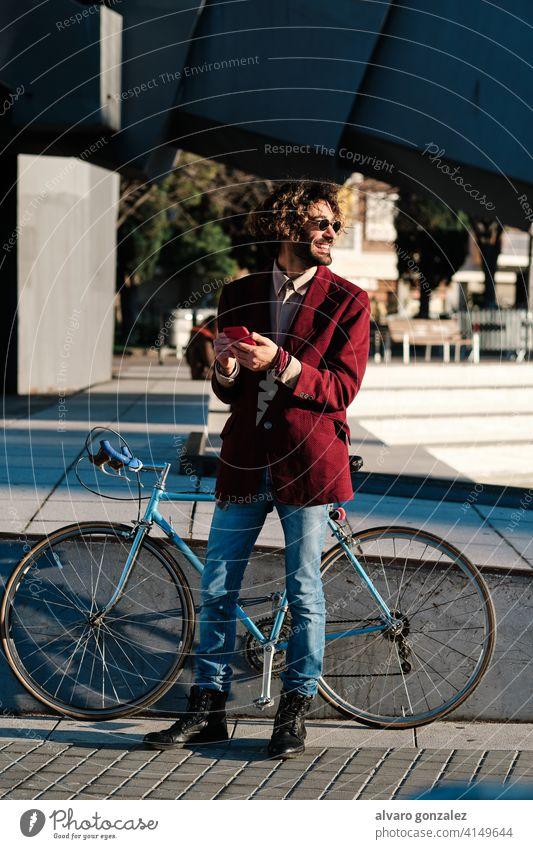 Hipster-Mann, der sein Mobiltelefon im Freien benutzt. Mobile Telefon Fahrrad Smartphone urban Großstadt Lifestyle Drahtlos Anschluss Mitteilung stylisch trendy
