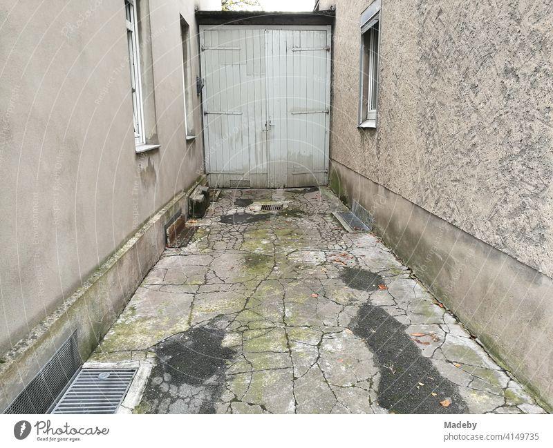 Enge Hofeinfahrt mit rissigen Steinplatten und altem Holztor einer Garage in Lemgo bei Detmold in Ostwestfalen-Lippe Tor Garagentor Platten Risse Erosion kaputt