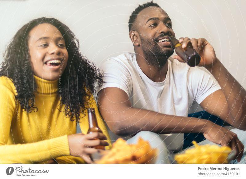 afro-amerikanisches Paar lächelnd und Bier trinkend zu Hause Glück heimwärts Afrikanisch Freunde Freundin jung Zusammensein Frau schwarz Alkohol Lächeln Mädchen