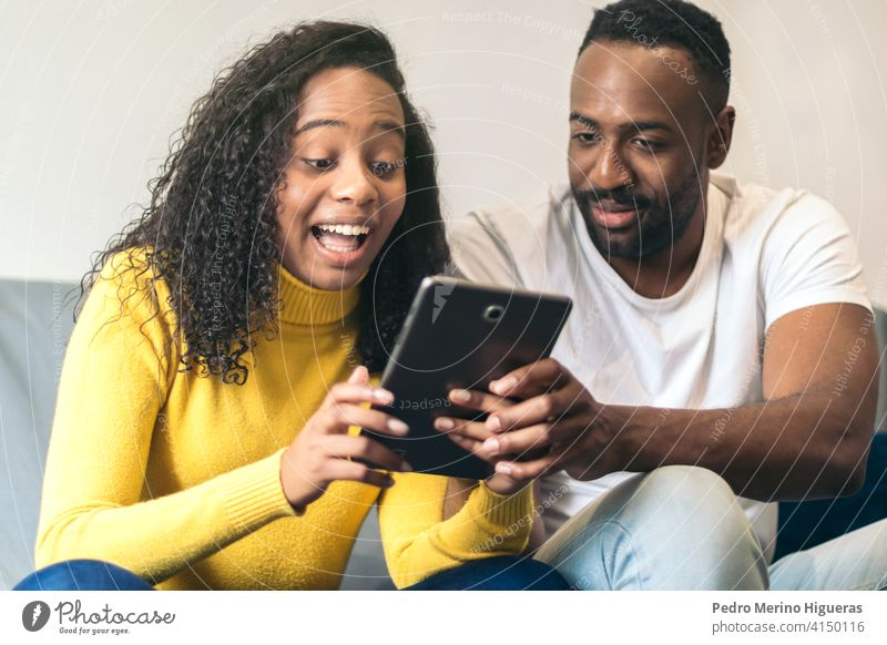 afroamerikanisches Paar, das Tablet zu Hause beobachtet Mann heimwärts Frau Internet schwarz Menschen Glück Technik & Technologie Tablette Lächeln jung