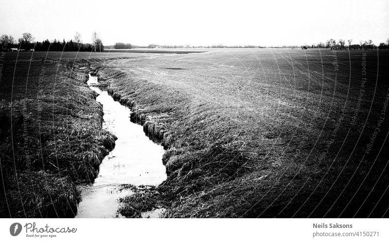 Ein kleiner Fluss, der im April durch Wiesen und landwirtschaftliche Felder fließt Athmosphäre Hintergrund schön Blues Gelassenheit Kanal Sauberkeit Cloud