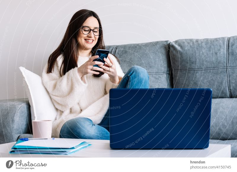Frau im Gespräch mit Handy während der Arbeit mit Laptop sitzt auf einer Couch zu Hause im Innenbereich benutzend arbeiten Büro Job Notebook jung Glück Tippen