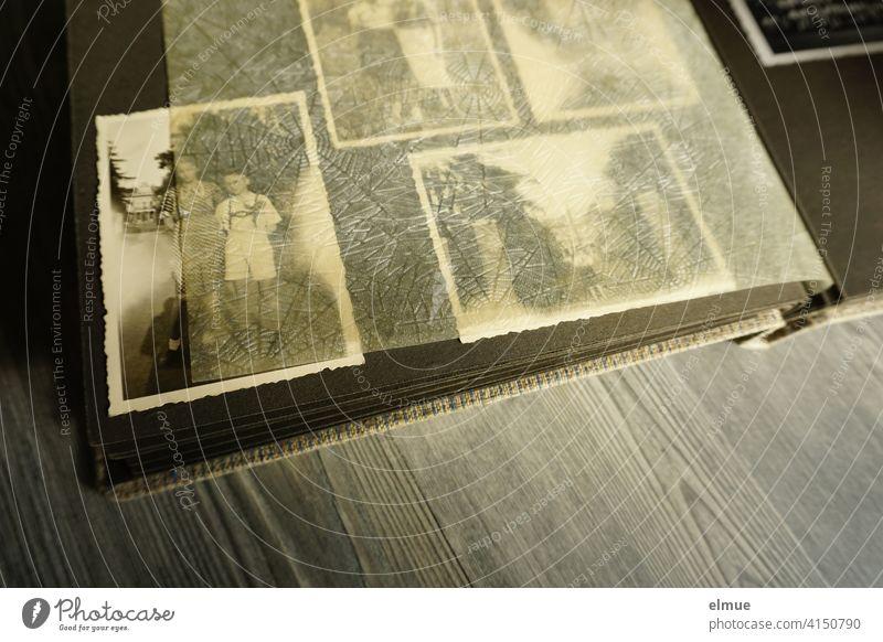 Blick in ein altes Fotoalbum mit schwarz-weiß Fotografien und Pergamentpapier zwischen den schwarzen Seiten / analoge Fotografie / Demenztherapie Papierbild