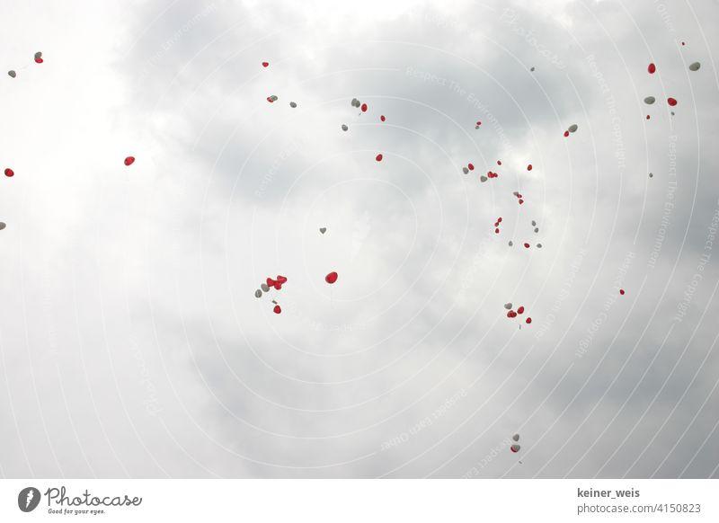 Rote und weiße Luftballons im grauen bewölkten Himmel herzförmig rot Zettel Karten viele fliegen Hochzeit Wolken Wetter Regenwetter Menge schweben romantisch
