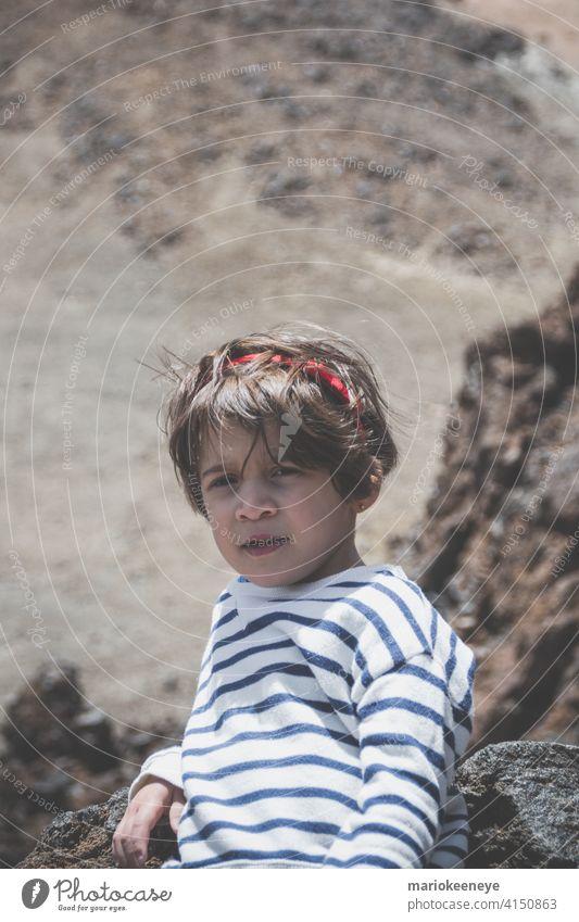 Porträt eines kleinen kaukasischen Mädchens mit kurzen Haaren mit einem vulkanischen Hintergrund Ruhe besinnlich eine Person nachdenklich Haarschnitt vertikal