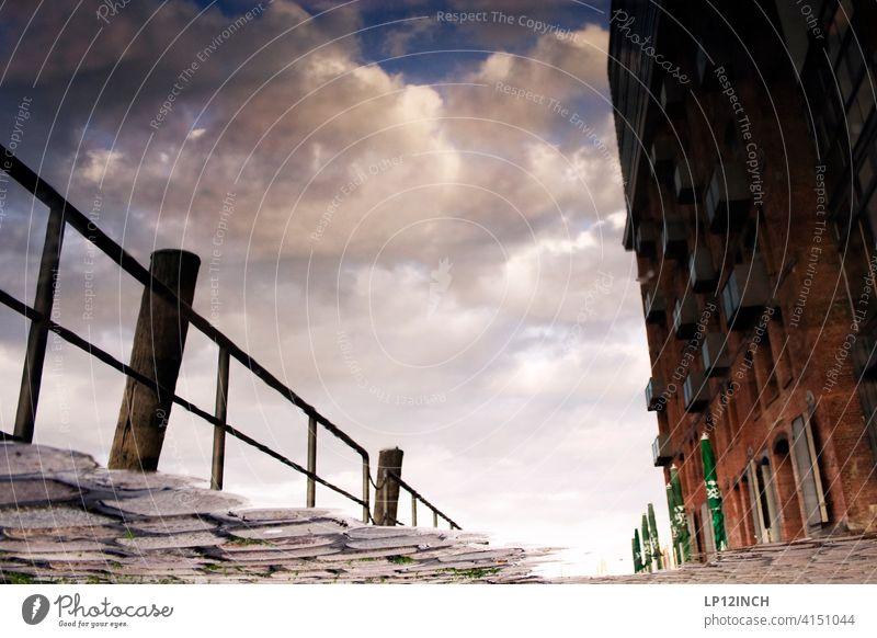 Pfütze an den Landungsbrücken Hamburg Reflexion & Spiegelung Geländer Haus Hafen Gebäude Bodenbelag perspektivwechsel Surrealismus surreal Architektur