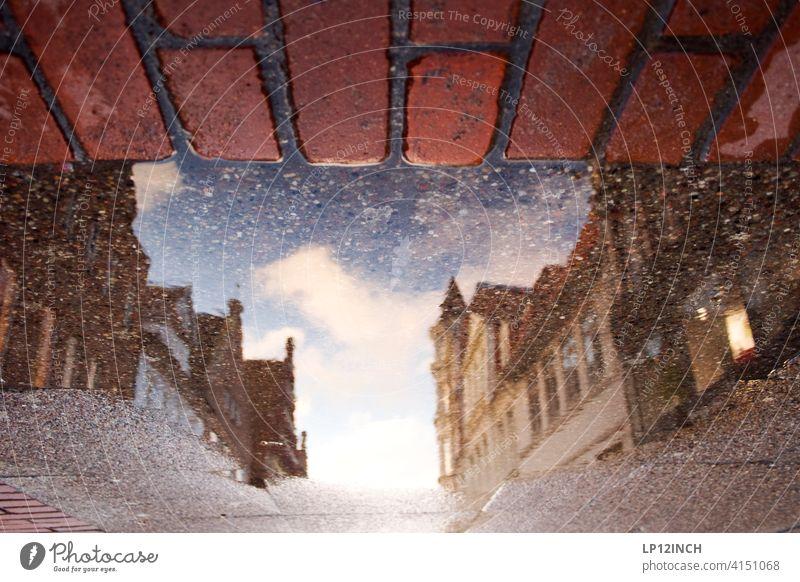 Lüneburger Einkaufsmeile Pfütze Stadt Spiegelung im Wasser Pfützenfoto Haus Altstadt Gebäude Städtereise Einkaufsstraße Boden surreal Backstein Regen wohnen