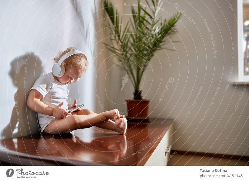 Ein Kind mit Kopfhörern schaut in ein Smartphone. Das helle Interieur im skandinavischen Stil zeigt eine eingetopfte Dattelpalme. Die Strahlen der Morgensonne im Raum. Technik und Menschen konzipieren Musik zu Hause. Raum kopieren.