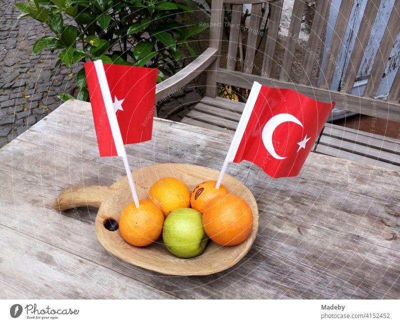 Orangen mit einem grünen Apfel und roten türkischen Wimpeln in einer Holzschale auf einem alten Holztisch mit Holzbank in den Gassen der Altstadt von Alacati bei Izmir in der Türkei