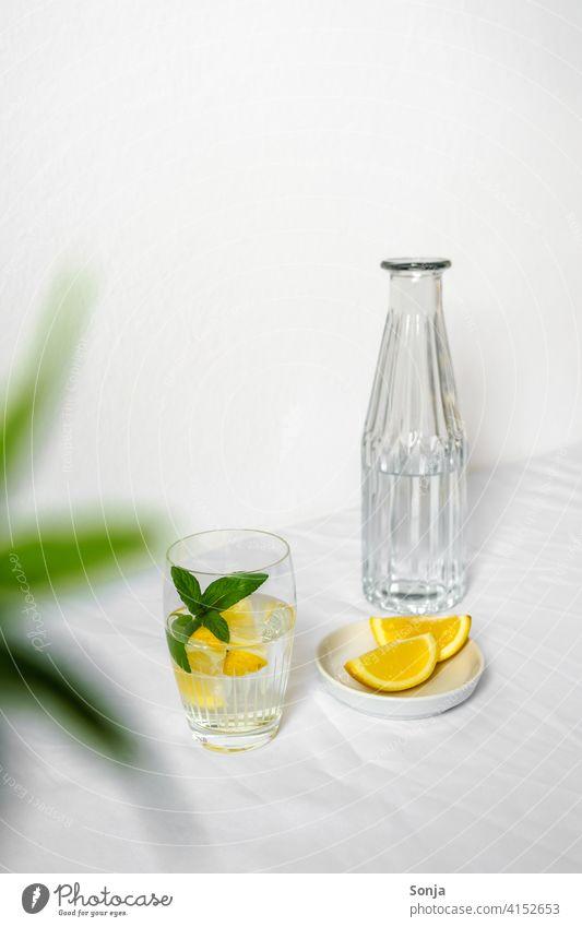 Eine Wasserflasche und ein Trinkglas mit Wasser, Zitrone und Pfefferminze auf einem weißen Tischtuch Erfrischungsgetränk Limonade gelb Zitronenscheibe Glas
