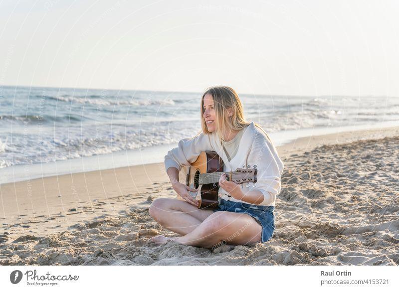 Junge kaukasische Frau spielt Akustikgitarre auf Sandstrand.Reise Lebensstil, Sommerurlaub Hintergrund mit Kopie Raum. Gitarre Spielen Strand Musik Lifestyle