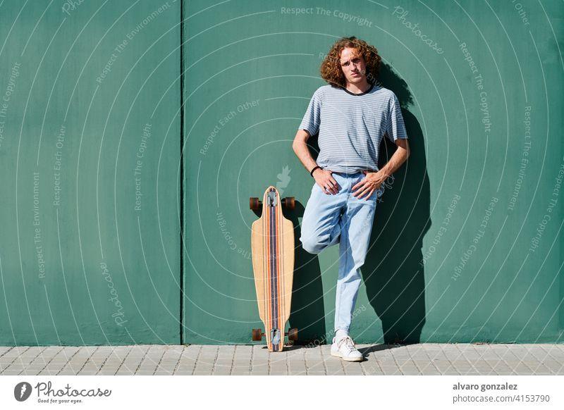 ein junger Mann mit lockigem Haar, der an einem sonnigen Tag mit seinem Skate- oder Longboard an einer grünen Wand steht che Skateboard attraktiv Person