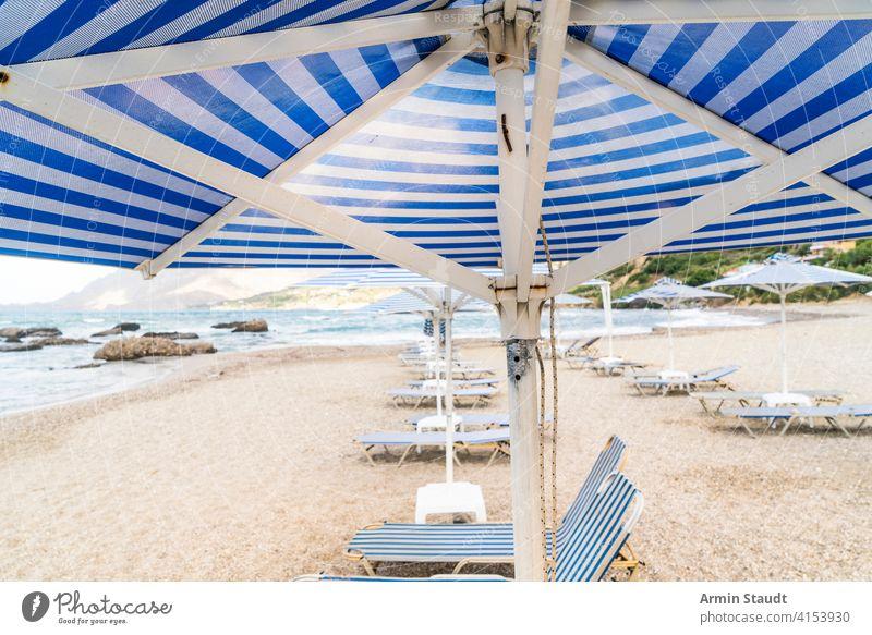 Liegestühle und Sonnenschirme an einem leeren Strand Hintergrund Bucht blau Stuhl Wolkenlandschaft Küste Küstenlinie Schiffsdeck Liegestuhl Feiertag Reise