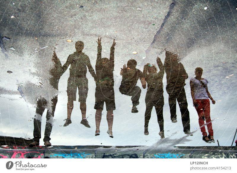 Pfützen sprung Teamgeist Menschen Gruppe Gruppenzwang Spiegelung 7 springen Spaß haben surreal Freunde Freundschaft Zusammenhalt Abheben starten