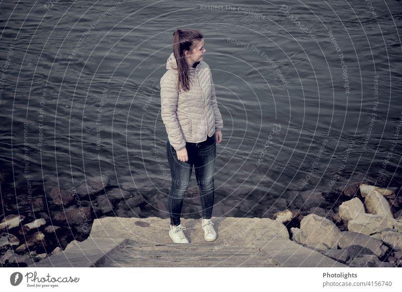 Junge Frau steht am Ufer eines Flusses jung Steine Steintreppe Wasser dunkel düster alleine Natur Außenaufnahme Farbfoto Landschaft Pferdeschwanz einsam