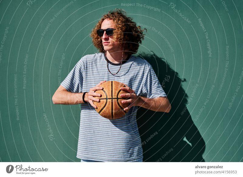ein junger Mann mit einem Basketball und Sonnenbrille mit einer grünen Wand im Rücken, der in die Sonne schaut che Ball Person Korb Sport sportlich männlich