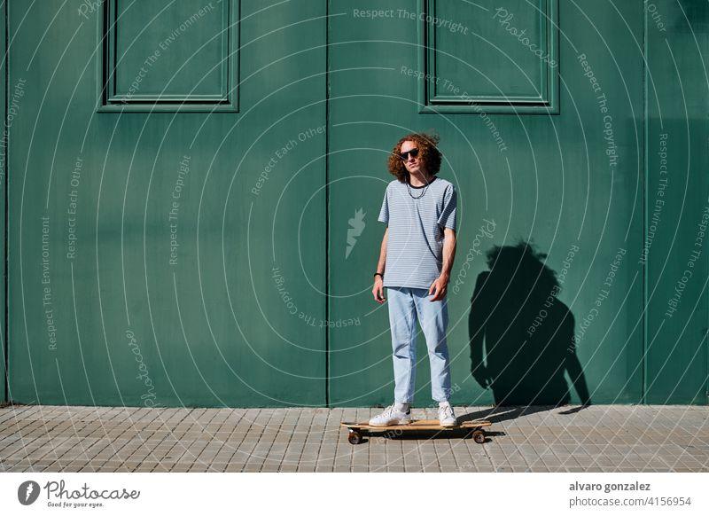 ein junger Mann mit lockigem Haar, der im Freien Schlittschuh läuft, mit einer grünen Wand hinter ihm Longboard che Skateboard attraktiv Person Skateboarding