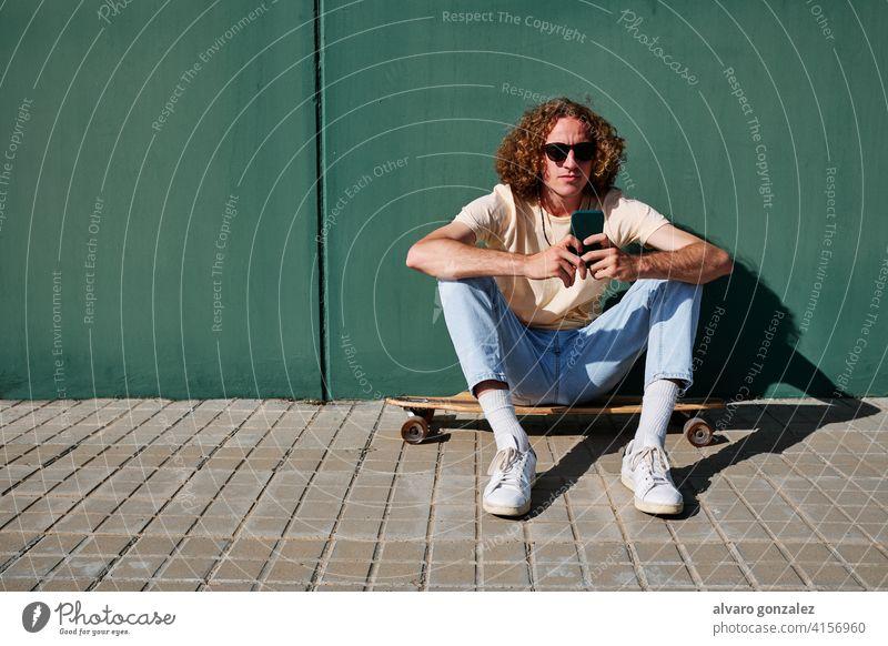 ein junger Mann, der sein Smartphone benutzt und auf seinem Skateboard oder Longboard sitzt, mit einer Wand im Rücken che attraktiv Person Skateboarding Sport