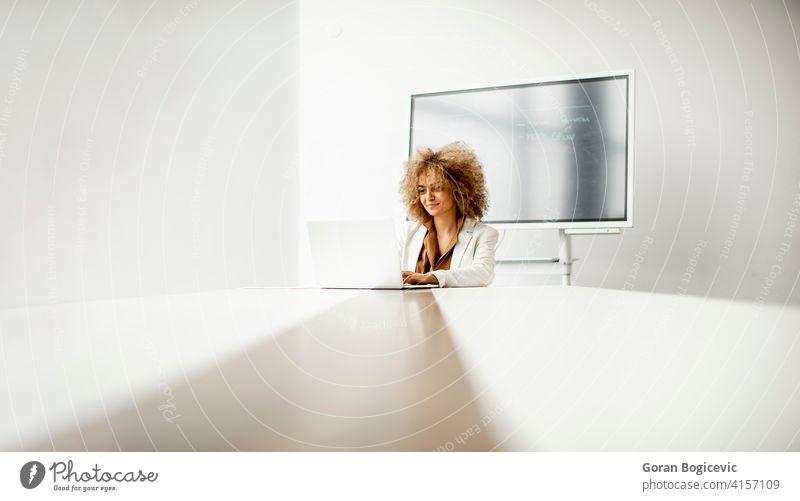 Afroamerikanische Geschäftsfrau sitzt und arbeitet am Laptop im modernen Büro Erwachsener Afrikanisch Afro-Look Amerikaner schön schwarz Business selbstbewusst